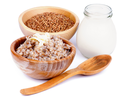 Arrangement of Traditional Russian Buckwheat Kasha with Buckwheat in Wooden Bowl, Milk Jar and Wooden Spoon isolated on white background