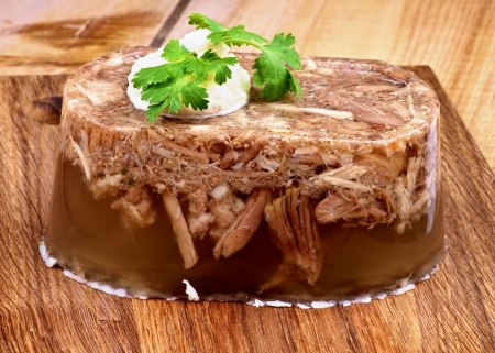 Delicious Homemade Aspic with Beef and Pork, Garlic and Spices Garnished with Horseradish and Parsley closeup on Wooden Cutting Board Foto de archivo