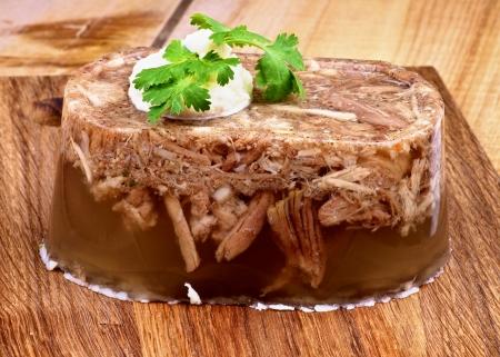 Hecho en casa delicioso Aspic con carne y carne de cerdo, ajo y especias adornado con rábano y perejil primer plano sobre tabla de cortar de madera