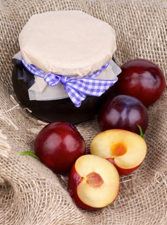 Arrangement of Jar of Plum Jam and Ripe Purple Plums Full Body and Halves closeup on Burlap  photo