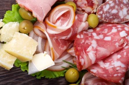 Disposición de las Cortes Charcutería frías con jamón ahumado, Varias salchichas, queso delicioso y aceitunas verdes portarretrato en madera oscura Foto de archivo
