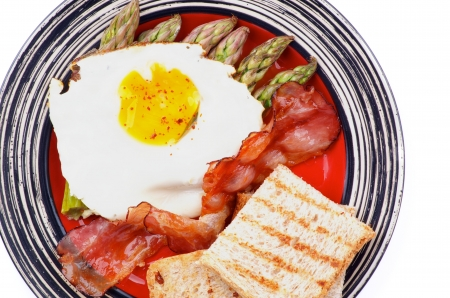 Tasty Breakfast with Fried Egg Sunny Side Up on Delicious Asparagus Sprouts, Roasted Bacon and Toasts on Striped Plate closeup on white  photo