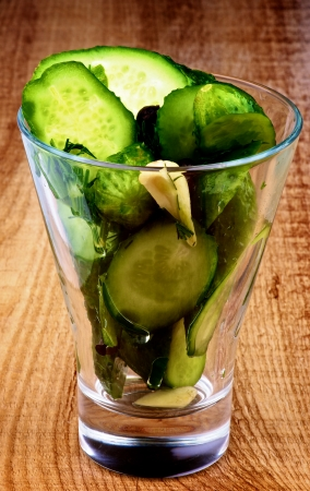 black peppercorn: Appetizer with Slices of Delicious Pickled Cucumbers in Brine of Garlic, Dill, Parsley and Black Peppercorn in Glass isolated on Wooden  Stock Photo