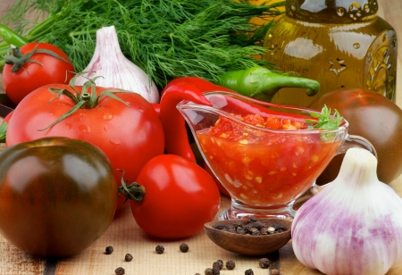 Arrangement of Bruschetta Sauce in Glass Gravy Boat with Black Tomatoes, Garlic, Chili Peppers and Olive Oil in Glass Bottle closeup on Wooden Horizontal View photo
