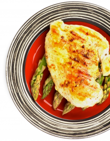 Delicious Roasted Chicken Breast with Asparagus Sprouts on Red Striped Plate closeup on white Top View Foto de archivo