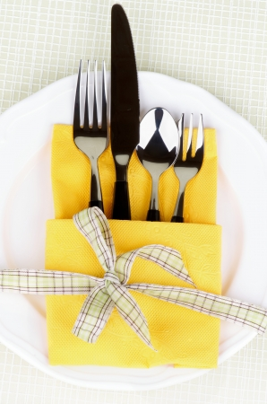 Spoon and Dessert Fork into Yellow Napkin Decorated with Green Checkered Bow on White Plate photo