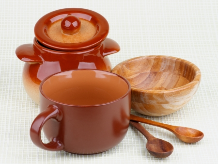 Arrangement Brownish Stoneware Pot, Wooden Bowl, Soup Porringer and Wooden Spoons. photo