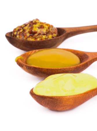 mustard plant: Wooden Spoons with Honey, Dijon and Whole Grain Mustards In a Row on white background