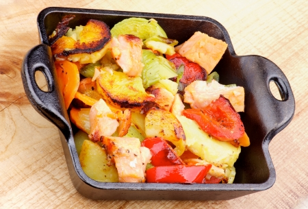Delicious Homemade Salmon Stew with Potato, Red Bell Pepper, Leek and Carrot in Black Frying Pan closeup on Wooden background photo