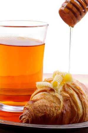 dripped: Freshly Baked Croissant with Butter, Honey Dripped from Wooden Dipper  and Cup of Tea closeup
