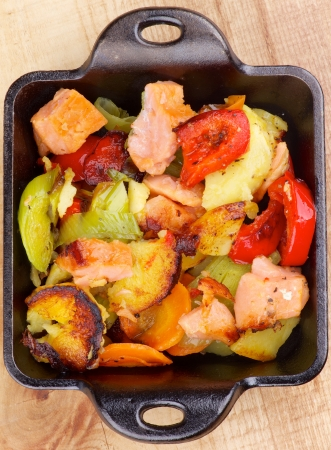 Tasty Homemade Salmon Stew with Potato, Red Bell Pepper, Leek and Carrot in Black Frying Pan on Wooden Top View photo