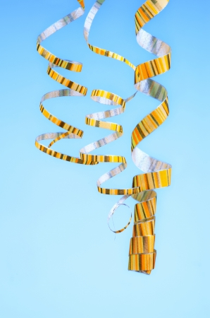 Three Yellow Striped Hanging Down Curled Party Streamers isolated on Blue  photo