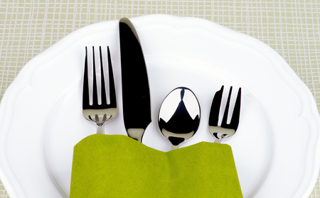 Elegant Table Setting with Fork, Table Knife, Spoon and Dessert Fork into Green Napkin Decorated on White Plate closeup on Checkered background  photo