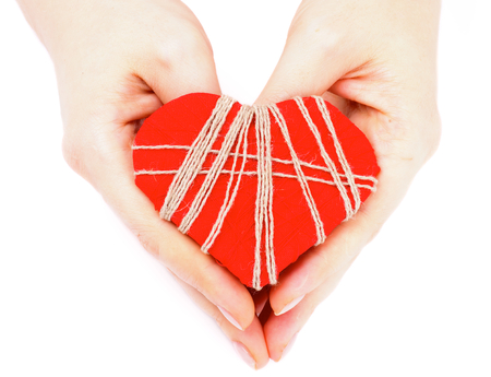 Handmade Valentine Red Heart Decorated with Threads in Woman Hands isolated on white background photo