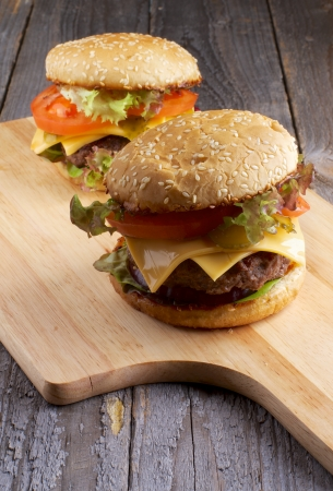 Two Tasty Hamburgers with Beef, Tomato, Lettuce, Pickle, Red Onion and Cheese into Sesame Buns closeup on Wooden Cutting Board photo