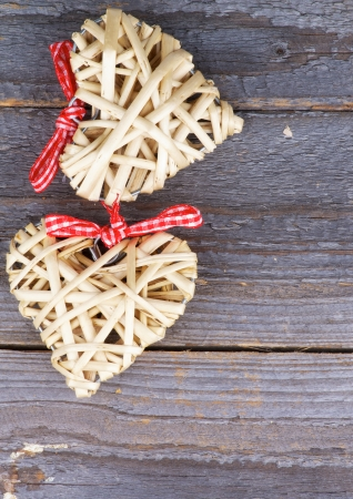 Arrangement of Two Handmade Wicker Hearts with Red Checkered Bows isolated on Rustic Wood background  Top View photo