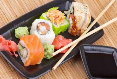 Arrangement of Various Maki Sushi with Salmon, Eel, Green Caviar and Crab on Black Plate with Soy Sauce and Pair of Chopsticks on Straw mat background photo