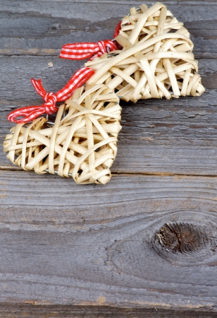 Two Handmade Wicker Hearts with Red Checkered Bows isolated on Rustic Wood background photo