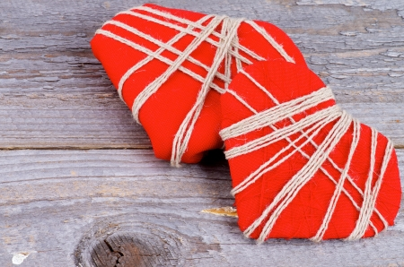 overlapped: Two Handmade Red Valentine  Hearts Decorated with Threads Overlapped on Rustic Wood