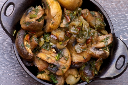 Delicious Champignon Mushrooms Stew with Onion and Greens in Black Cast Stock Photo - 25199669