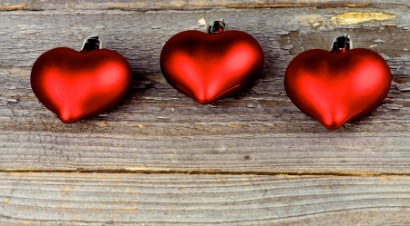 Three Red Plastic Hearts In a Row closeup on Rustic Wood surface photo