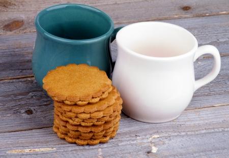 galletas de jengibre: Dos tazas de t� con Pila de galletas de jengibre aislados sobre fondo de madera r�stica