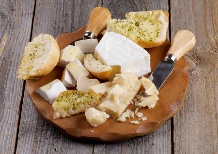 tabla de queso: Tabla de quesos con deliciosa Camembert, Brie, queso parmesano y ajo Pan y cuchillos de queso primer plano sobre fondo de madera r�stica