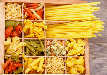 Various Raw Dry Pasta in Wooden Box closeup photo