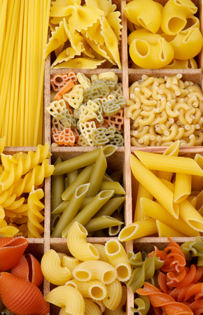 maccheroni: Various Raw Dry Pasta closeup in Wooden Sections