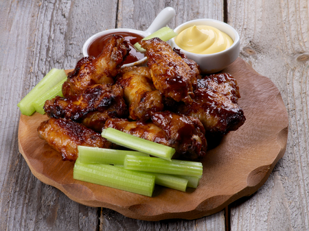 Chicken Legs and Wings Barbecue with Ketchup and Cheese Sauces and Celery Sticks on Wooden Plate closeup photo