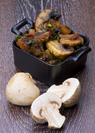 Delicious Roasted Edible Champignon Mushrooms in Black Cast-iron Stew Pots and Halves of Raw Mushrooms isolated on Wooden background photo