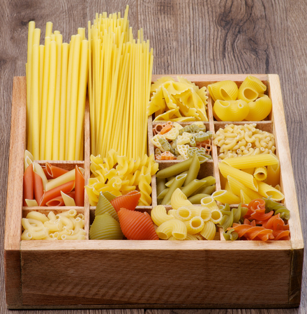 Various Raw Dry Pasta in Wooden Box closeup  Vertical View photo