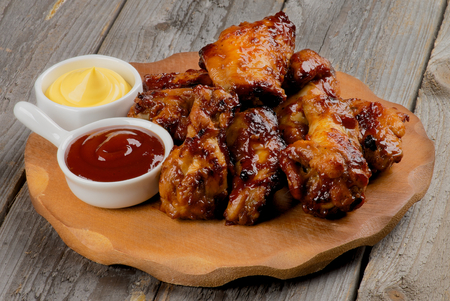 Chicken Legs and Wings Barbecue with Sauces on Wooden Plate closeup on Rustic Wooden background