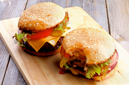 Two Ripe Hamburgers with Beef, Tomato, Lettuce, Pickle, Red Onion and Cheese into Sesame Buns Full Body and Nipped closeup on Wooden Cutting Board photo