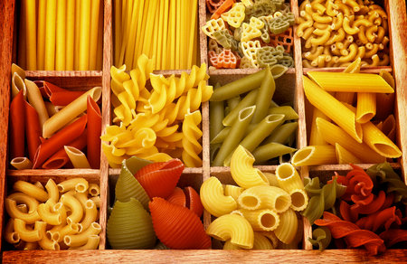 Various Raw Dry Colorful Pasta with Pasta Shells and Fusillini closeup in Wooden Sections photo