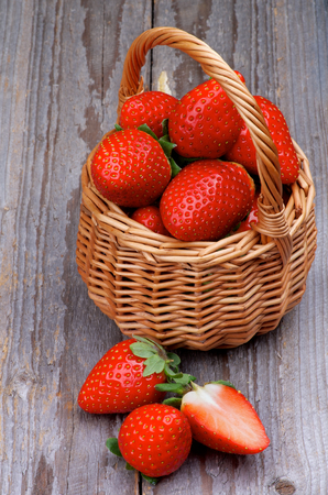 Wicker Basket with Fresh Ripe Strawberries closeup on Rustic Wooden background photo