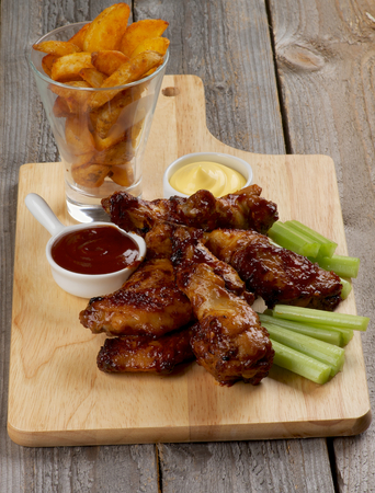 Juicy Chicken Legs and Wings Barbecue with Ketchup, Cheese Sauce, Celery Sticks  and French Fries in Glass closeup on Wooden Cutting Board photo