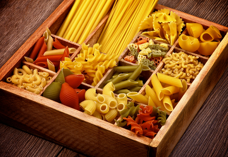 Various Raw Dry Pasta in Wooden Box Cross Section on Rustic Wooden background photo
