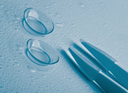 Arrangement of Two Contact Lenses with Water Droplets and Special Tweezers isolated on Wet background  Blue Toned photo