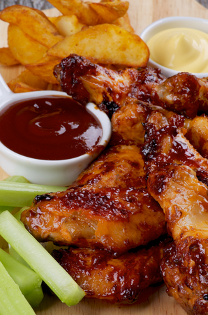 Juicy Chicken Legs and Wings Barbecue with French Fries, Ketchup, Cheese Sauce and Celery Sticks closeup on Wooden Board