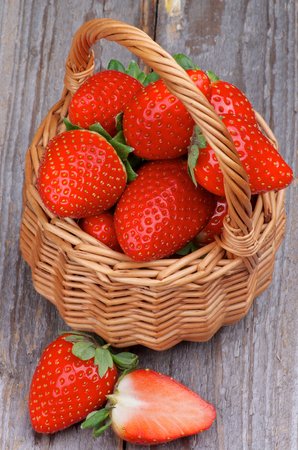 Ripe Strawberries Full of Wicker Basket closeup on Rustic Wooden background photo