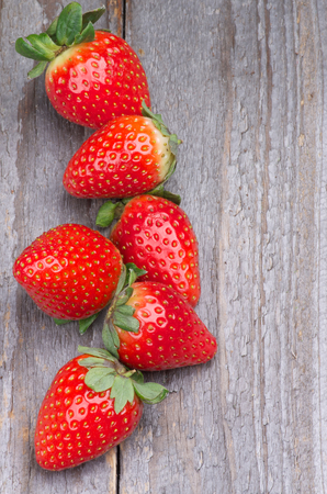 Ripe Strawberries Full Body In a Row isolated on Wooden background  Top View photo
