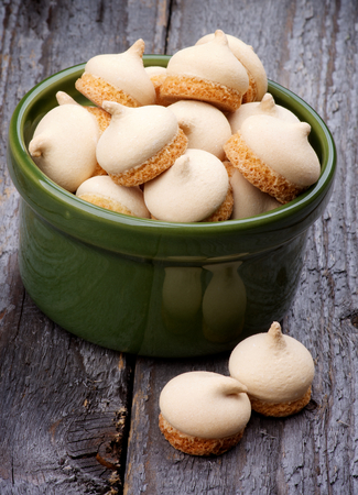 twiddle: Delicious Swirled Meringue Topping in Green Bowl isolated on Rustic Wooden background Stock Photo