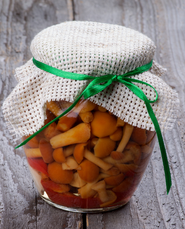 canned food: Delicious Marinated Forest Mushrooms in Glass Jar isolated on Rustic Wooden background