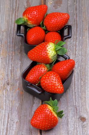 forme carre: Heap de Perfect premi�res fraises dans Carr� noir sur fond isol� bols en bois rustique