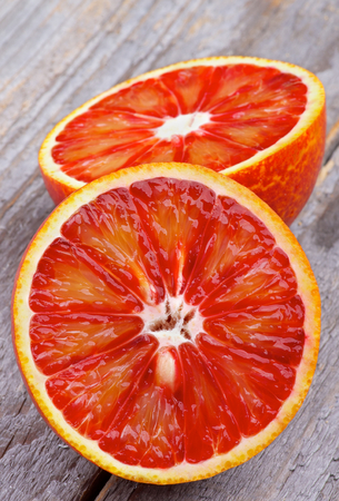 Two Halves of Ripe Blood Oranges closeup on Rustic Wooden background