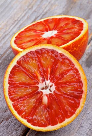 Dos mitades de naranjas maduras de la sangre de primer plano sobre fondo de madera rústica