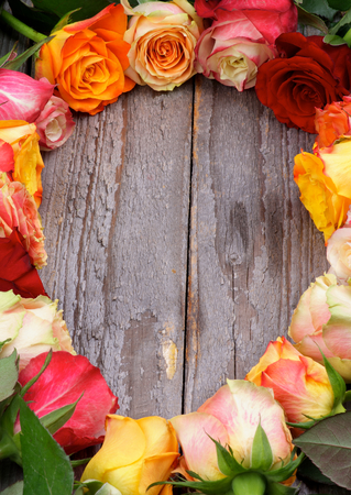 Ellipse Frame of Mixed Colorful Roses with Leafs closeup on Rustic Wooden background  Vertical View photo