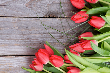 Corner Frame of Beautiful Spring Red Tulips with Green Grass isolated on Rustic Wooden background  Top View photo