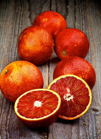 body and blood: Arrangement of Ripe Full Body Blood Oranges with Two Halves isolated on Rustic Wooden background